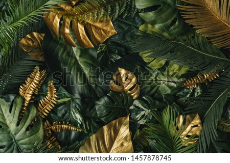 Creative nature background. Gold and green tropical palm leaves. Minimal summer abstract jungle or forest pattern.