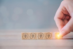 Creative new business idea and innovation concept. Hand choosing wooden cube block with light bulb and wood blocks with human head symbol on wood table background. Abstract conceptual business