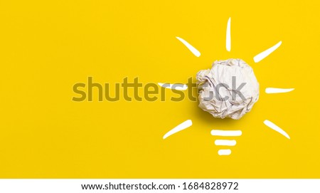 Creative new idea. Innovation, brainstorming, inspiration and solution concepts. Light bulb with crumpled paper on yellow background.