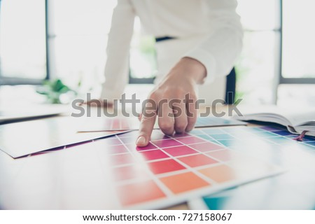 Creative occupation. Close up of hand of female graphic designer, interior designer, architect, stylist, she is choosing the colors for new project, stopping her attention on purple one #727158067