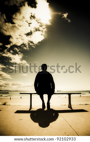 Creative Outdoor Photo Of A Young Man In Silhouette Sitting In The Sun On A Park Bench At A Australian Beach, Photograph Taken Wategos Beach, Byron Bay Australia