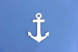 Creative paper cutout of traditional anchor made of white paper on blue background