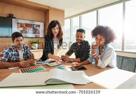 Creative people looking at project plan laid out on table. Mixed race business associates discussing new project plan in modern office.