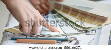 Creative people workplace. Close-up view of hands of young designer woman working with color palette at office desk. Interior shot. Horizontal photo banner for website header design