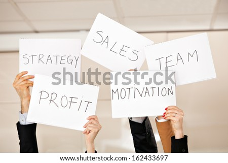 creative photo: five hands holding card boards in the air: strategy, motivation, profit, team, sales
