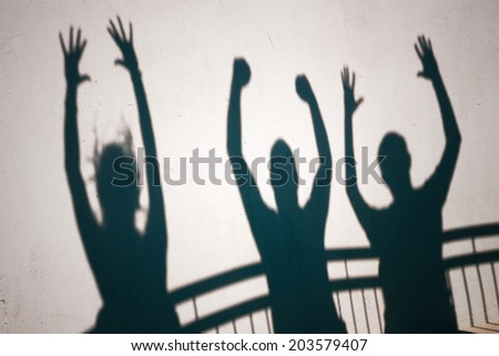 Creative photo of ecstatic people shadows on white wall