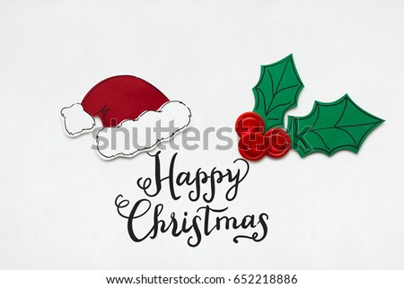 Creative photo of santas hat and holly berry made  of paper on white background. #652218886