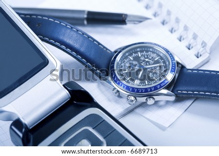 Creative photo: telephone, wrist-watch, notepad and fountain-pen