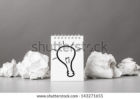 creative process. crumpled wads and notebook with bulb picture