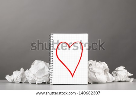 creative process. crumpled wads and notebook with heart picture