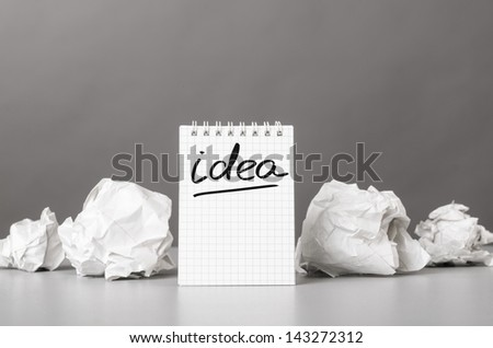 creative process. crumpled wads and notebook with word idea