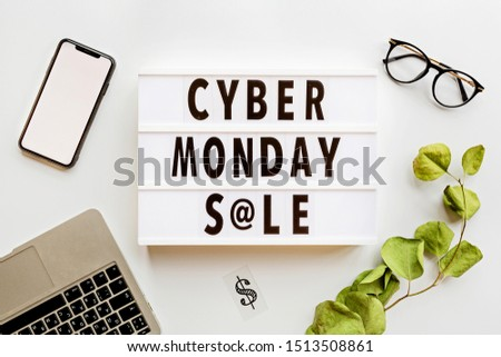 Creative promotion composition Cyber monday sale text on lightbox, laptop, mobile phone, eyeglasses, eucalyptus branch on white background. Flat lay, top view, overhead, mockup, copy space, template