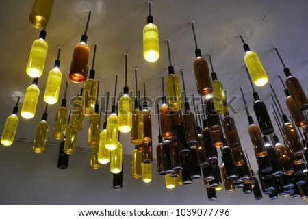 Creative reuse of wine bottles as lamps installed on the ceiling