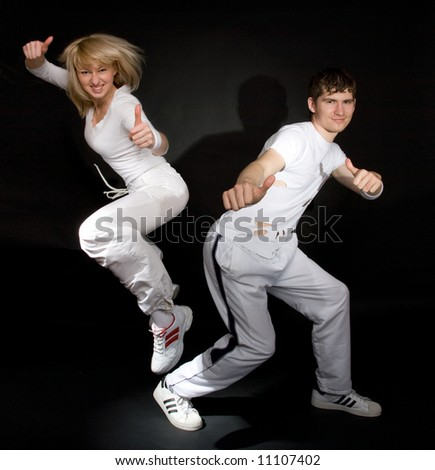 Creative shot of couple doing break-dance and showing positivity. Not isolated. Light shadows on the walls.