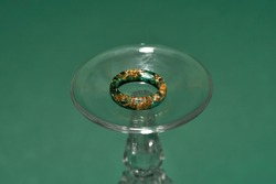 Creative shot of stylish handmade ring made of epoxy resin with golden foil inside on wine glass isolated over green background. Jewelry fashion photography, making jewelry concept