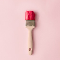 Creative spring concept made with paint brush and red tulip flower on pastel pink background. Minimal nature flat lay.
