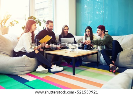 Creative staff of graphic design company brainstorming on informal meeting sitting in coworking office using modern drone.Students reading literature preparing for writing university coursework