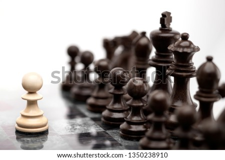 Creative success business concept meaningful photo of one pawn staying against full set of chess figures pieces on board. #1350238910