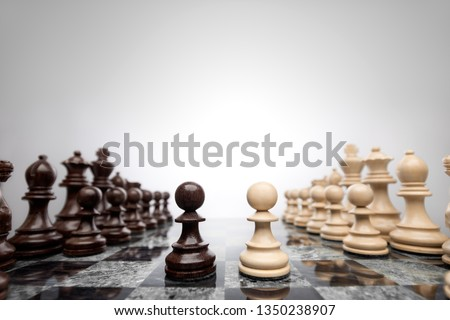 Creative success business concept meaningful photo of two pawns opposition in the middle of the checkerboard.