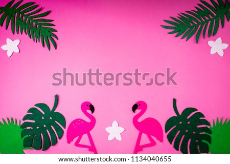 Creative summer background with flamingo and palm leaves on pink. Handmade palm leaves and birds. Felt toy. Top view