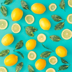 Creative summer pattern made of lemons and green leaves on pastel blue background. Fruit minimal concept. Flat lay.