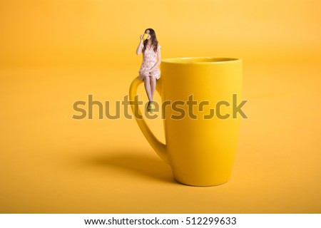 Creative surrealism design with miniature people. Girl with a cup. The girl in a pink dress sits on the mug. Yellow cup of tea or coffee. Young woman drinking tea. Mug on yellow background