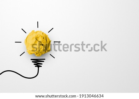 Creative thinking ideas and innovation concept. Paper scrap ball yellow colour with light bulb symbol on white background