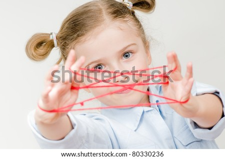 Creative thinking - little girl playing cats cradle game - stock photo