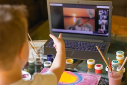 Creative toddler boy is creativity and the artist in an online drawing paints lesson. Childrens creativity. The concept of distance learning online school for the period of global quarantine.