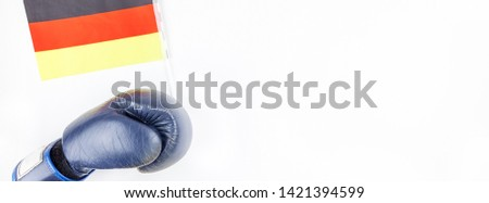 Creative top view flat lay of boxing glove with Germany flag and copy space on white background in minimal style. Concept of politic fights in Europe