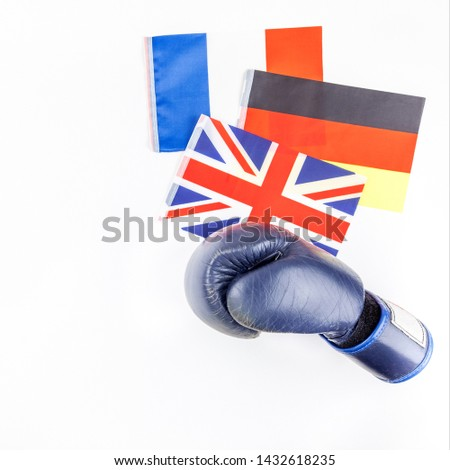Creative top view flat lay of boxing glove with Germany France and Great Britain flags and copy space on white background in minimal style. Concept of politic fights in Europe