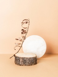 Creative trending composition with natural wood podium, round marble board and dry branch on pastel beige background. copy space. Front view?Podium for the presentation of various products