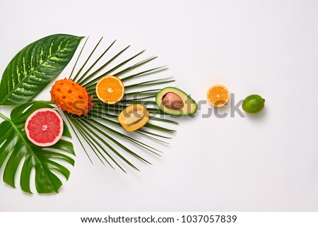 Creative Tropical Layout. Palm Leaves and Fresh Fruits. Colorful Summer Design Set. Healthy Art Food concept. Nature Bright background. Flat lay.