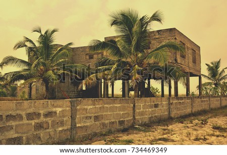 Creative vintage. Matte. Palm trees on a background of unfinished building. Abandoned house. Old photo. Retro