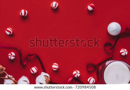Creative winter season flatlay on red background. Red stripe, white cotton flowers, peppermint candies, candles, coconut oil, body brush. Copy space. Beauty blog, announcement, ad layout concept #720984508