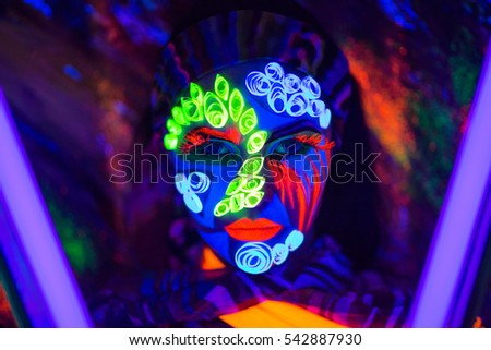 Creative woman lady girl model shine with blue green orange colors. New Bright conceptual art make-up glows under ultraviolet light. Club disco neon party time. Drink alcohol feel wild energy of music #542887930