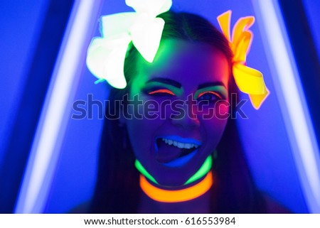 Creative woman model shine blue green orange colors. Bright conceptual art make-up glows under ultraviolet light. Club disco neon party time. Drink alcohol feel wild energy of music. Halloween horror #616553984
