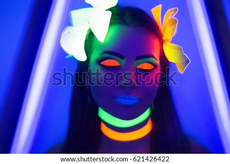 Creative woman model shine blue green orange colors. Bright conceptual art make-up glows under ultraviolet light. Club disco neon party time. Drink alcohol feel wild energy of music. Halloween horror #621426422