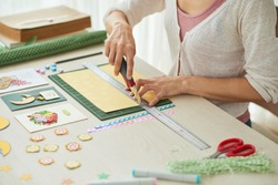Creative woman sitting at wooden table and making greeting cards for her friends, scrapbooking items lying on surface