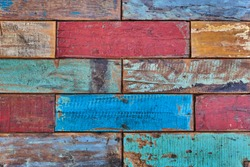 Creative wood background. Patterned and textures background of brightly colored planks. Room interior vintage with colorful wooden tiles. Art of colorful color on wooden wall. Weathered painted wood.