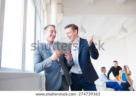 Creative work and technology. Two smiling handsome men using tablet computer while discussing something with their colleagues in the background. #274739363