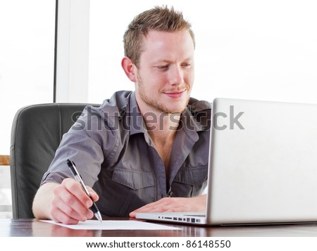 Creative worker smiling as he works on his laptop