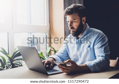 Creative worker using digital devices and programs in project. Corporate executive sitting at office desk, typing on laptop. Manager making important business phone calls on smartphone, checking email