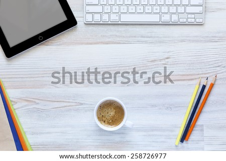 Creative working desk with coffee mug in the center. \ Top view on working place with cup of coffee, tablet PC, computer keyboard, and color matching booklets and pencils.