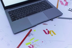 Creative workplace of a Graphic Designer with Laptop and logotype.