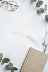 Creative workspace with paper notebook, glasses, eucalyptus leaves on marble background. Minimal style home office desk table. Flat lay, top view.