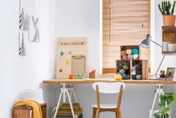 Creative workspace with scandinavian, wooden furniture, white walls and sewing tools in a modern crafts room interior. Real photo.