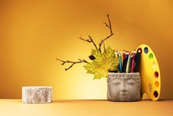 Creative yellow background with geometric podium for product presentation or exhibitions. Still life from the Head of Buddha and and watercolors and pencils.