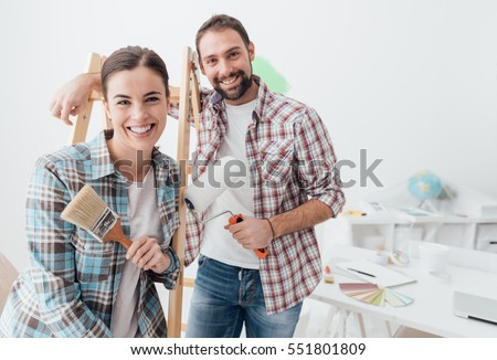 Shutterstock Creative young couple renovating their house and painting walls, they are posing together and smiling at camera