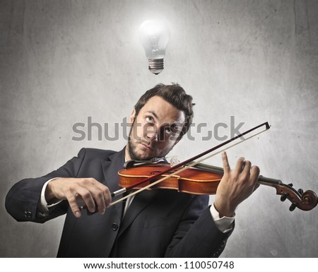 Creative young man playing the violin with light bulb over his head